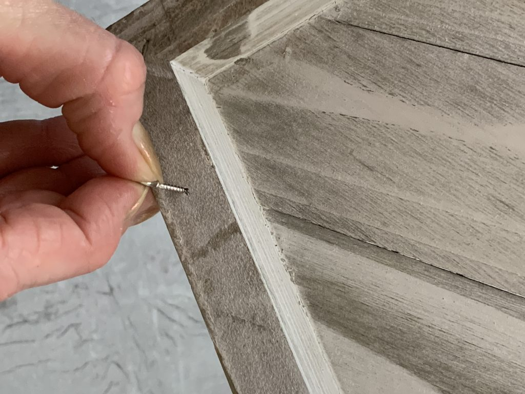 hand putting screw into wood board into winter wall decor