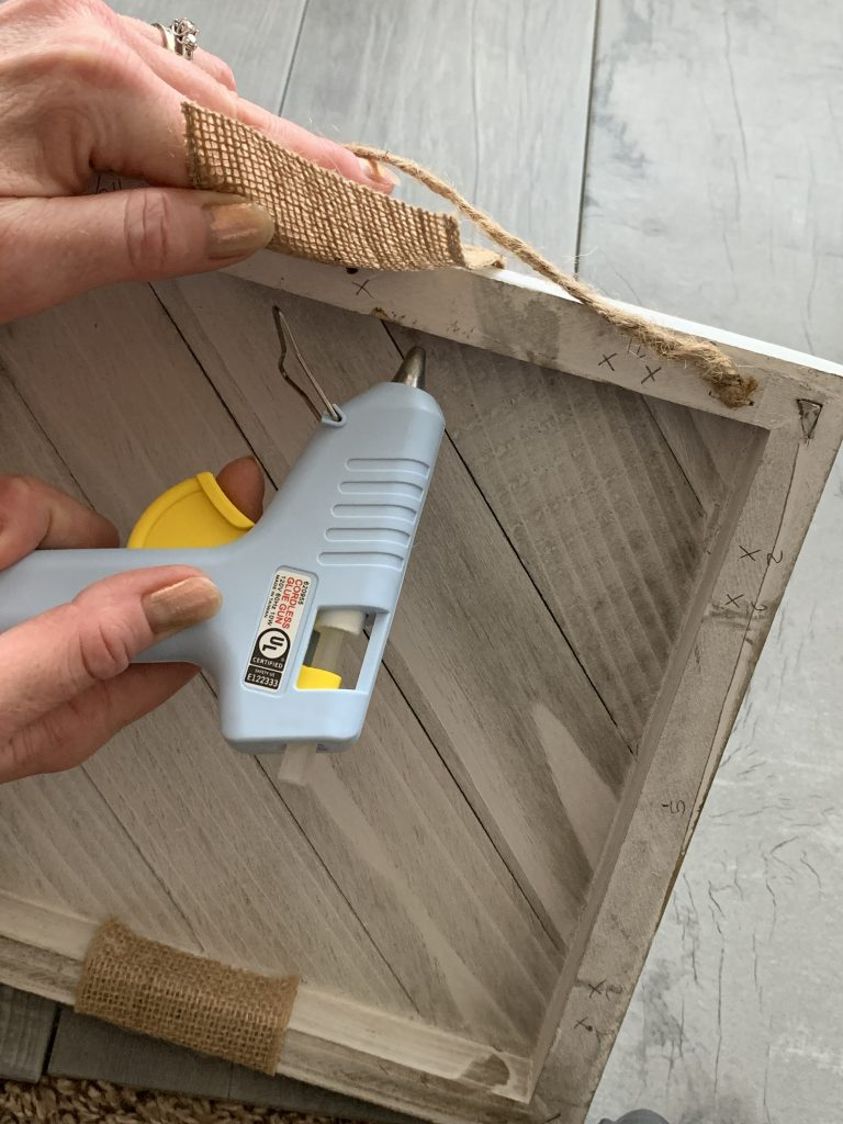 hot glue gun with burlap and white wood board