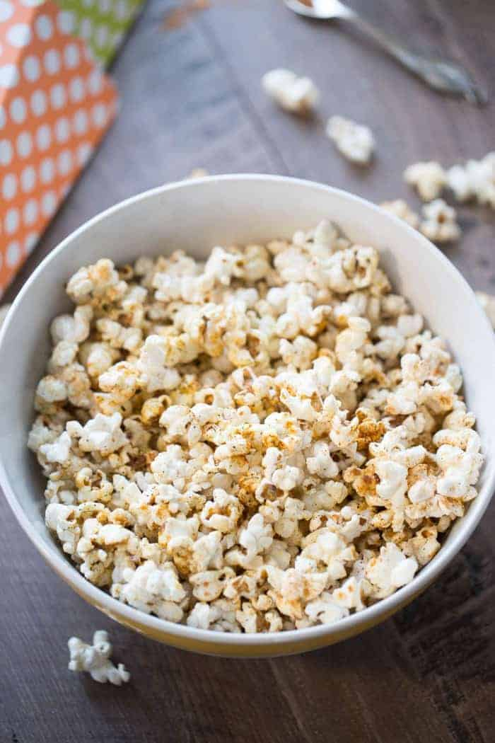 Homemade kettle corn recipe served with a sprinkling of BBQ seasoning in a large white bowl on a wooden table.