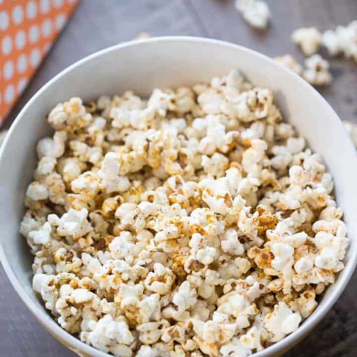 Delicious kettle corn with sugar and BBQ seasoning in a large white bowl on a wooden table.