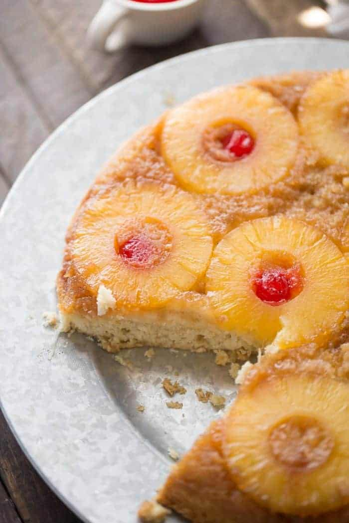 Upside down cake takes a tropical turn! This easy cake recipe has pineapple and cherries resting in a caramel sauce while the cake itself has shredded coconut and a hint of rum!