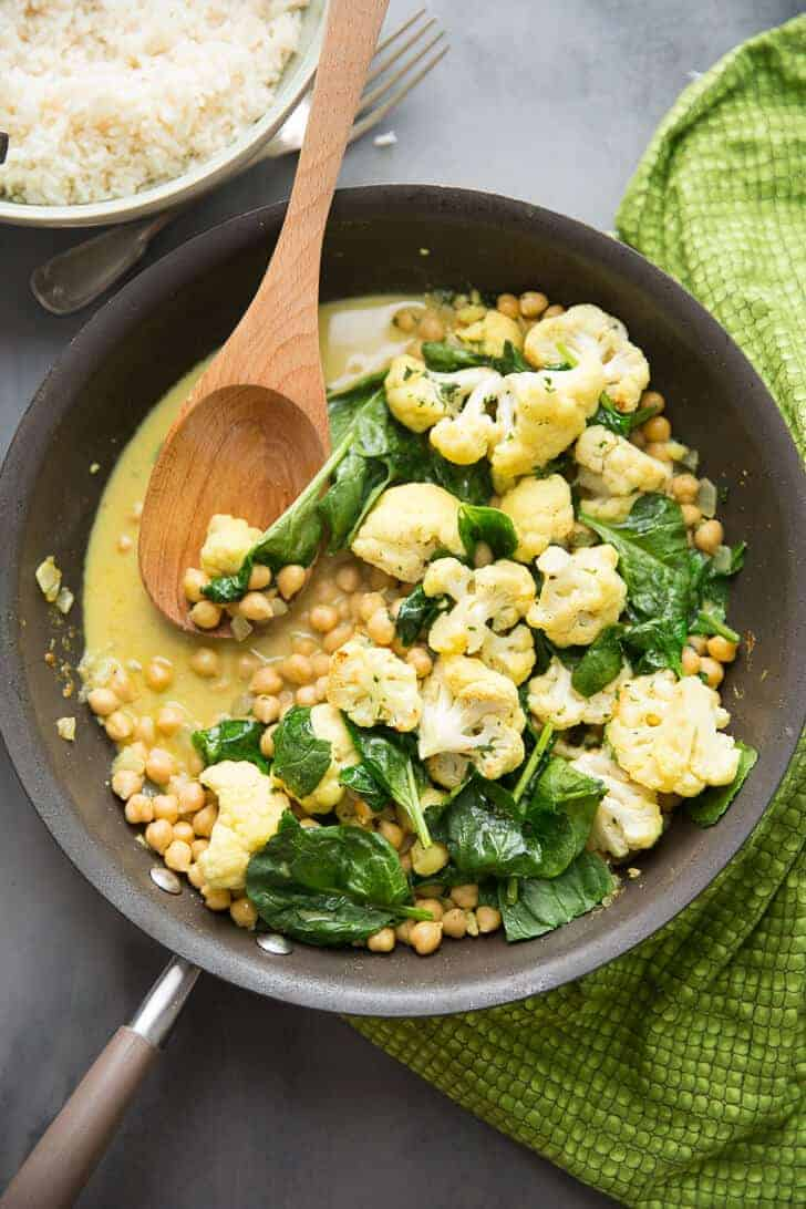 It's easy going meatless with this easy Vegetarian Curry. Cauliflower, garbanzo beans, and spinach are cooked in a coconut sauce that is rich and silky!