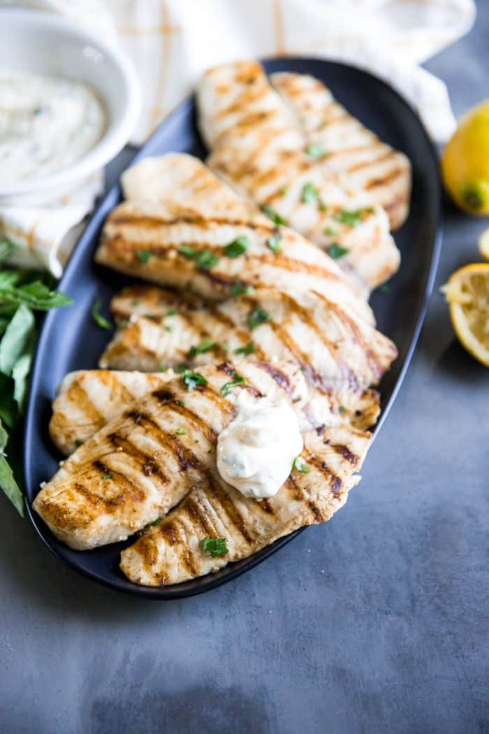 Grilled tilapia on platter with aioli