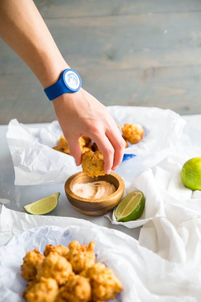 Hand dipping conch fritters
