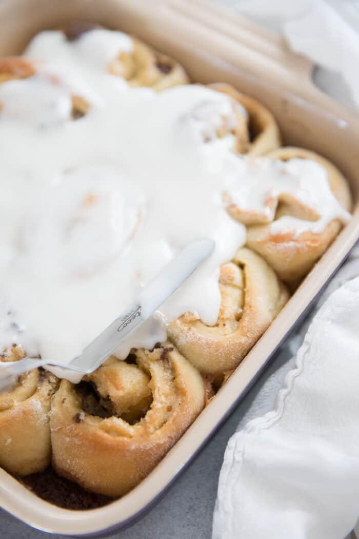 cinnamon rolls being iced