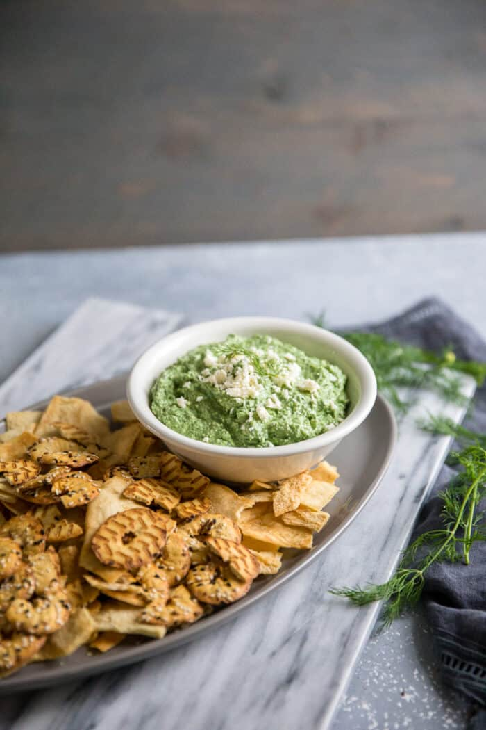 A bowl of food on a table, with Spinach dip
