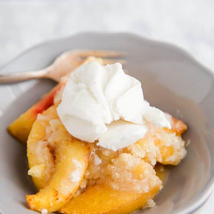 peach cobbler in a bowl with vanilla ice cream