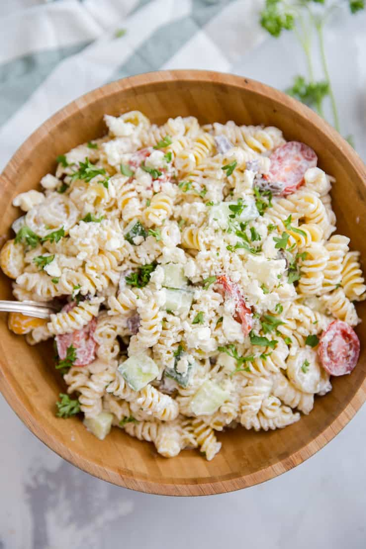 Greek pasta salad with a spoon resting in the bowl