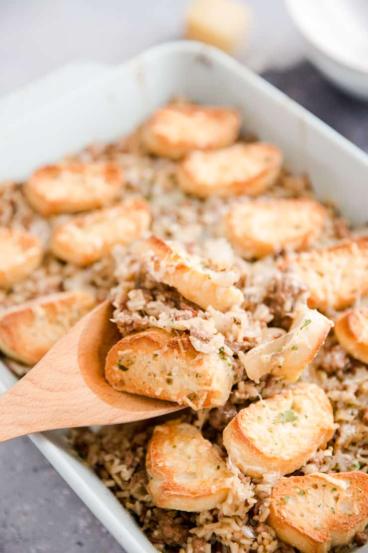ground beef casserole being served with wooden spoon