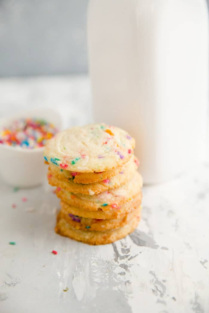 stack of butter cookies next to a milk jar