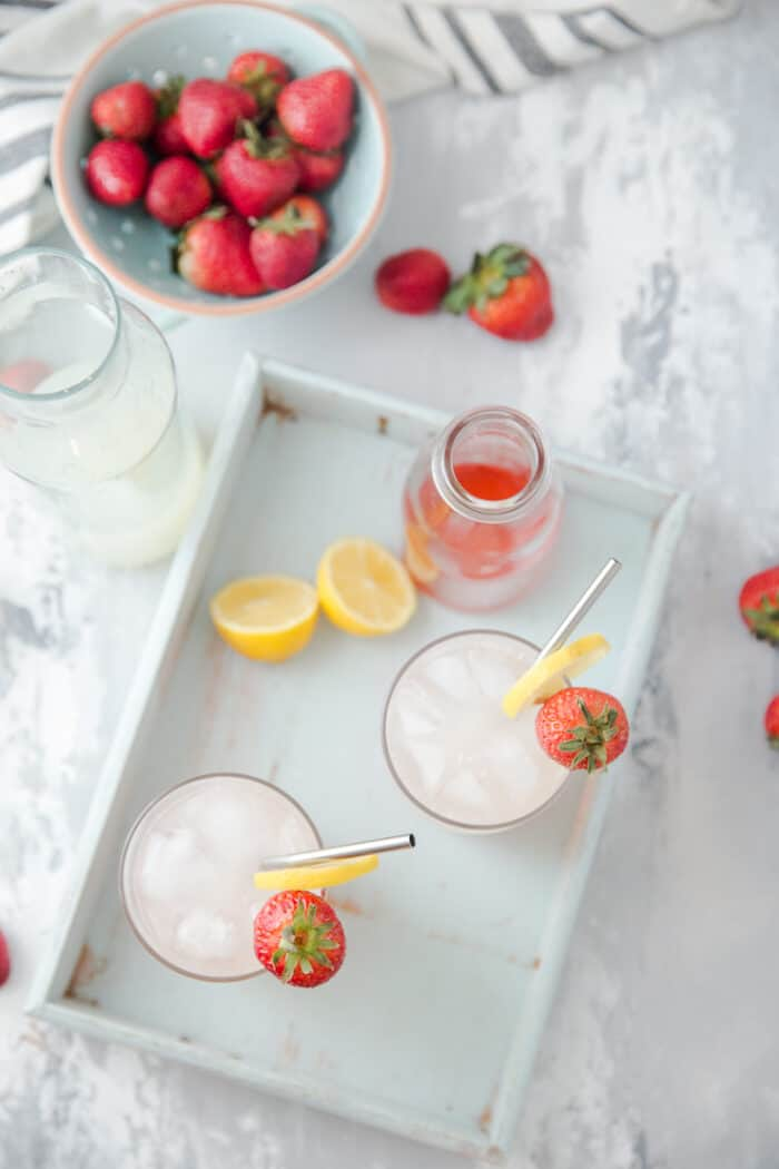 vodka lemonade glasses on a blue tray with strawberries on the side