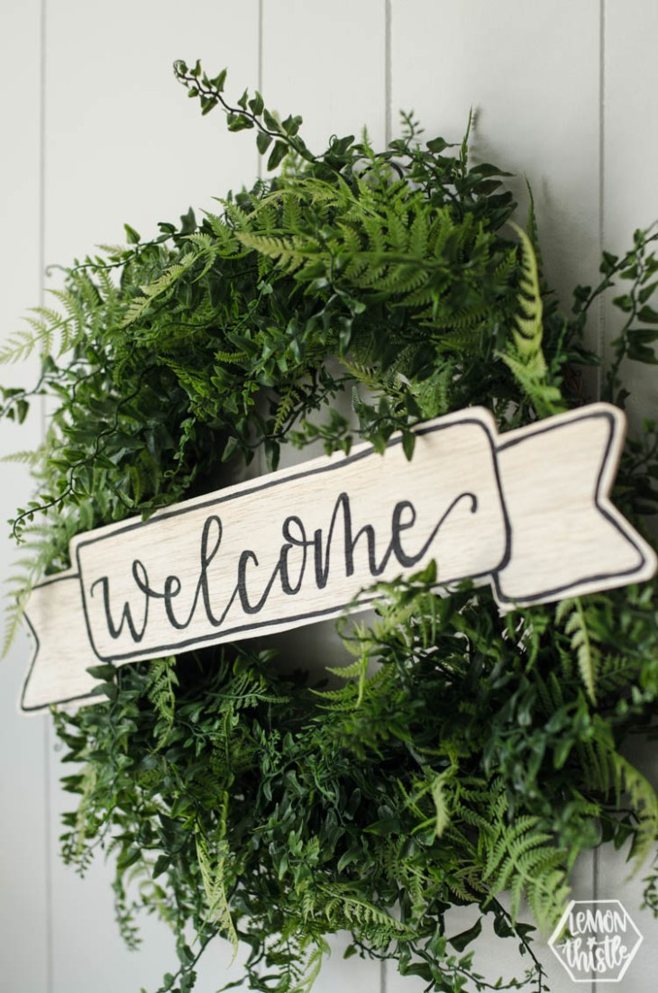 boxwood wreath with wooden welcome sign