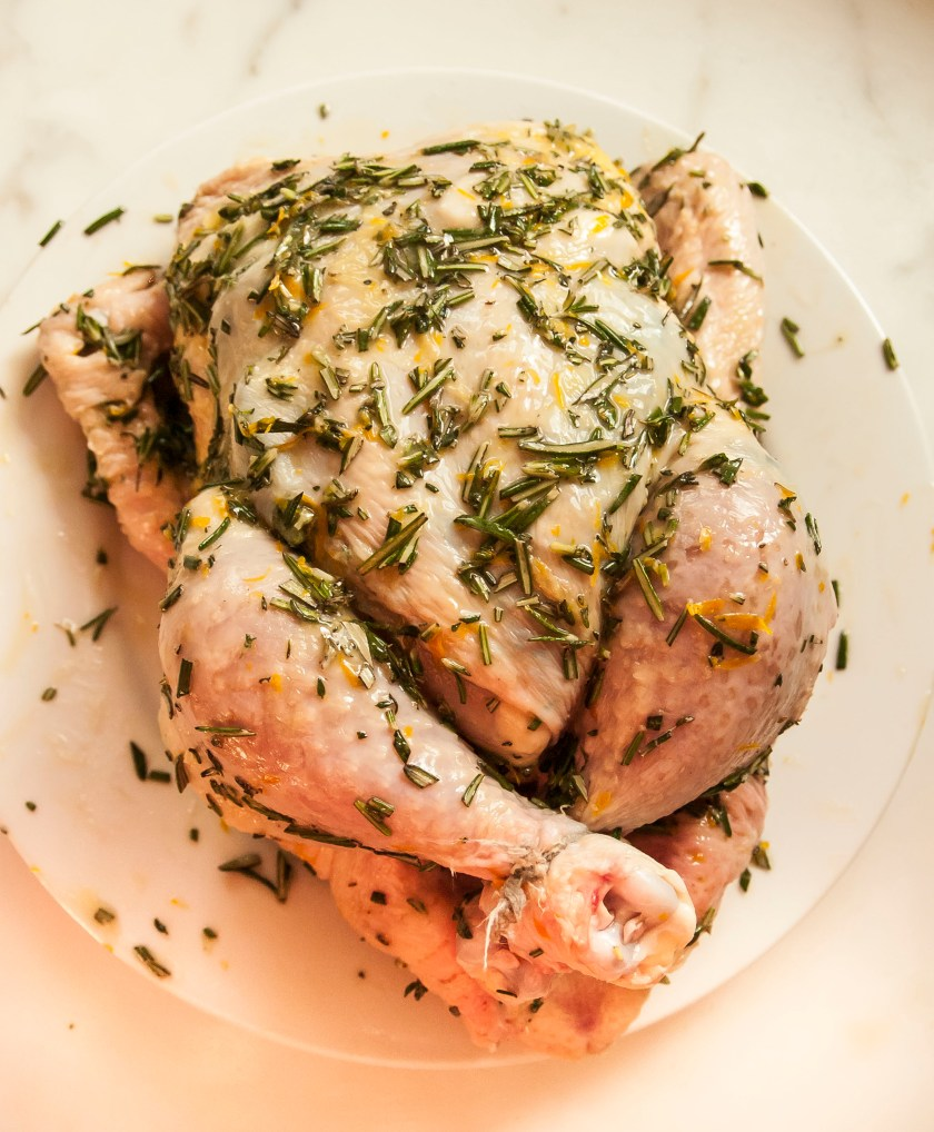 Roast Chicken Recipe with fresh herbs and lemons. The chicken is roasted on a bed of vegetables for a one pan meal and delicious pan sauce