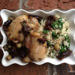 Overhead photo of Chicken Marbella with pearl couscous, green olives and prunes in a white baking dish on a brick background.