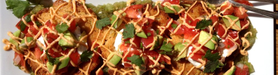 Sweet Corn Tamale Cakes on a white plate on a wooden board. Topped with diced tomatoes, avocado, and fresh cilantro.