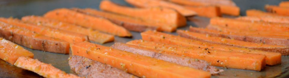 Oven baked Sweet Potato Fries sitting on a baking sheet. They bake up crispy and delicious.