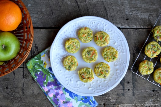 Mini Veggie Quiche that are Weight Watchers friendly. Eight mini quiche sitting on a white plate with more on a cooling rack. The plate is sitting on a wooden table with a colorful napkin and basket of fruit.