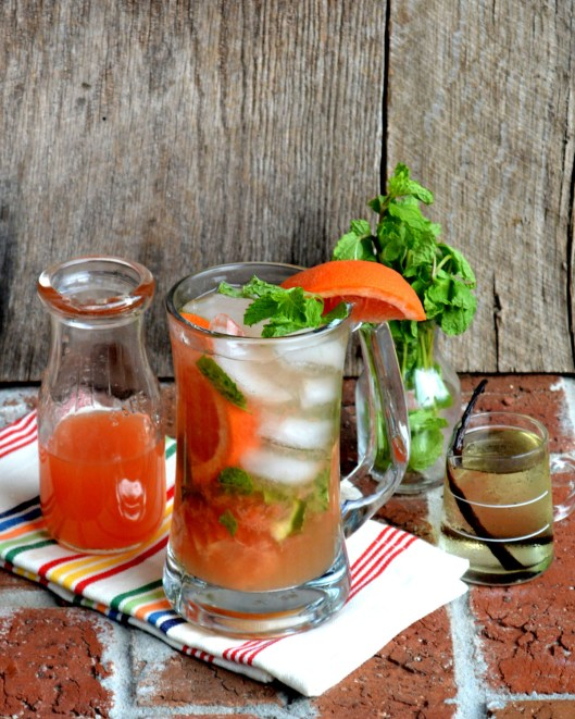 Red Grapefruit Mojito in a glass mug with Vanilla Simple Syrup in a small pitcher. Fresh mint and grapefruit juice are in small glass bottles.