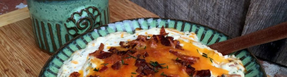 Loaded Baked Potato Dip with Crispy Baked Potato Wedges served in a green bowl sitting on a wooden table.
