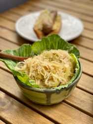 Closeup shot of a cabbage leaf lined bowl filled with sauerkraut. There's a brat with sauerkraut faded in the background.