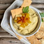 Overhead view of golden beet hummus in a white bowl with flatbread crackers.