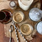 Overhead view of Iced Brown Sugar Oat Milk Shaken Espresso set up with two glasses of espresso and two glasses of ice, a pitcher of simple syrup and a bottle of oat milk. There are two paper straws and a spoon. All items are sitting on a piece of burlap sitting on a wooden block.