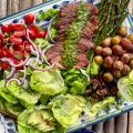 Overhead picture of large platter with lettuce leaves, sliced steak, little potatoes, mushrooms, asparagus, tomatoes and avocado. There's a small dish of chimichurri sauce.