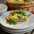 A slice of Sweet Potato Crust Veggie Quiche on a stack of white plates