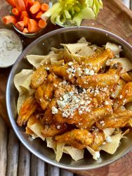 Closeup overhead shot of buffalo chicken wings over tortilla chips. Carrot and celery sticks in background.