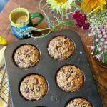 Overhead shot of six gluten free chunky monkey muffins with chocolate chips in muffin tin sitting on cooling rack on wooden table. There are wild flowers and a cup of coffee also pictured.