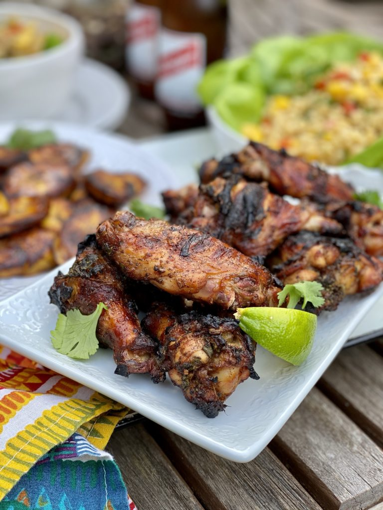 Beautifully grilled Jerk Chicken Wings on a white plate with colorful cloth napkin.