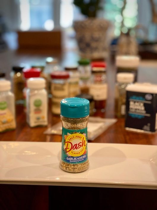 Picture of Mrs. Dash garlic and herb seasoning in front of a variety of space and seasoning jars.