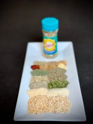 White plate with an assortment of ground spices lined up.