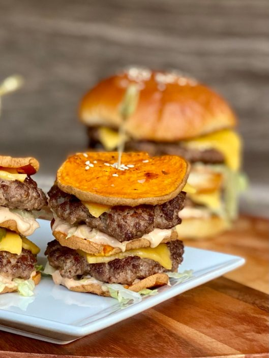 Close up of double Dekker cheeseburger made with sweet potato buns sitting on a white plate on a wooden board