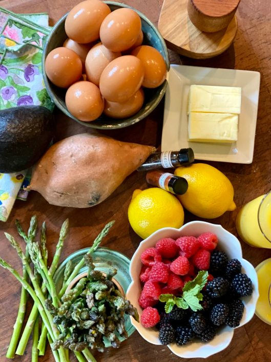 Sweet Potato Eggs Benedict Ingredients on a wood table with fresh berries and asparagus