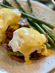 Eggs Benedict on white plate with side of asparagus