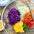 Caribbean Coleslaw Ingredients in a glass bowl, including purple and green cabbage, mango, red pepper, carrot and jalapeno.