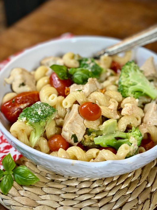 Easy Baked Feta & Tomato Pasta with Chicken & Broccoli in a white bowl with red and white floral napkin