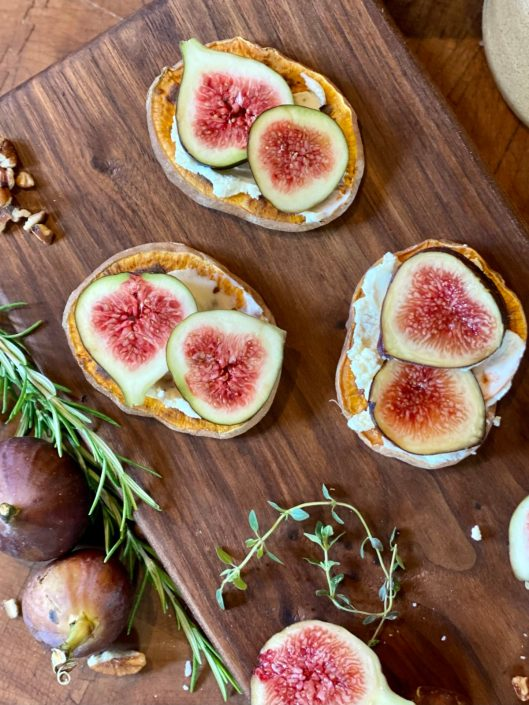 Fig & Mascarpone Sweet Potato Pizza with sliced figs on sweet potato rounds sitting on a wooden cutting board with fresh herbs