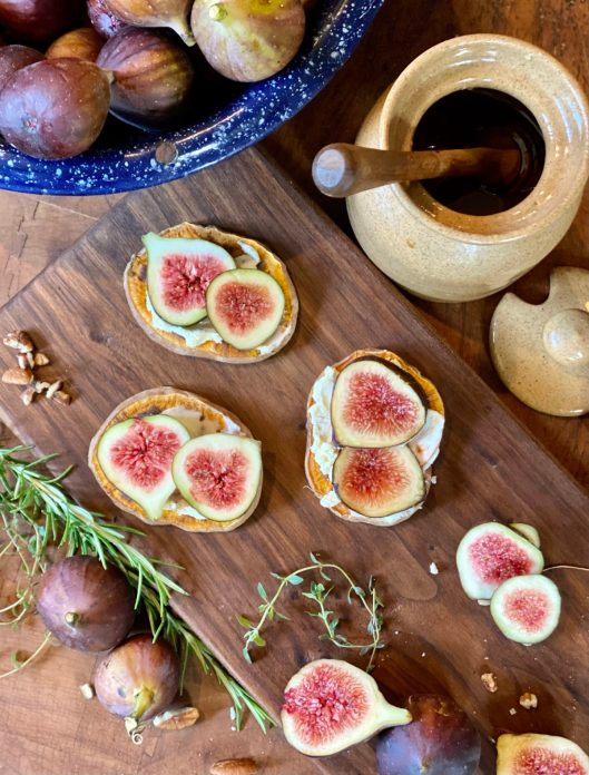 Overhead shot of sliced figs on mascarpone cheese on sweet potato rounds