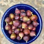 A blue metal bowl filled with fresh picked figs sitting on a stone