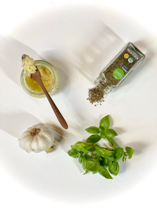 Overhead shot of fresh Basil vs. dried and fresh garlic vs. jarred