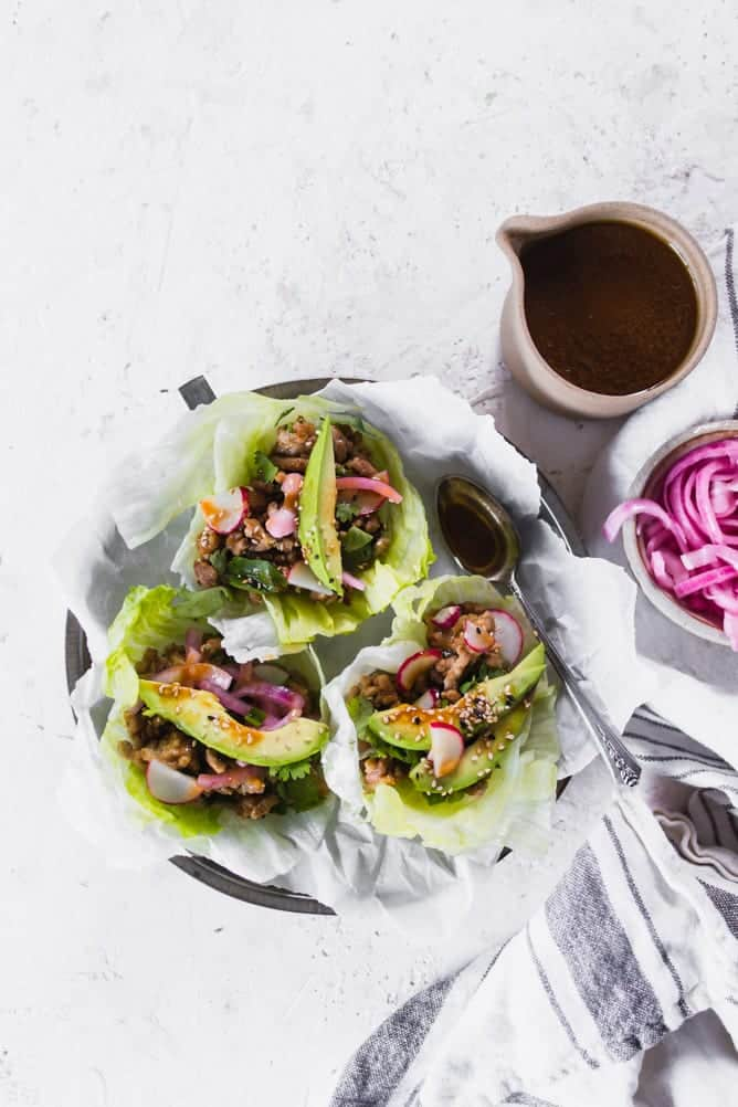 Low Carb Asian Pork Lettuce cups in small plates. Up close shot, topped with veggies and pickled onions. lenaskitchenblog.com