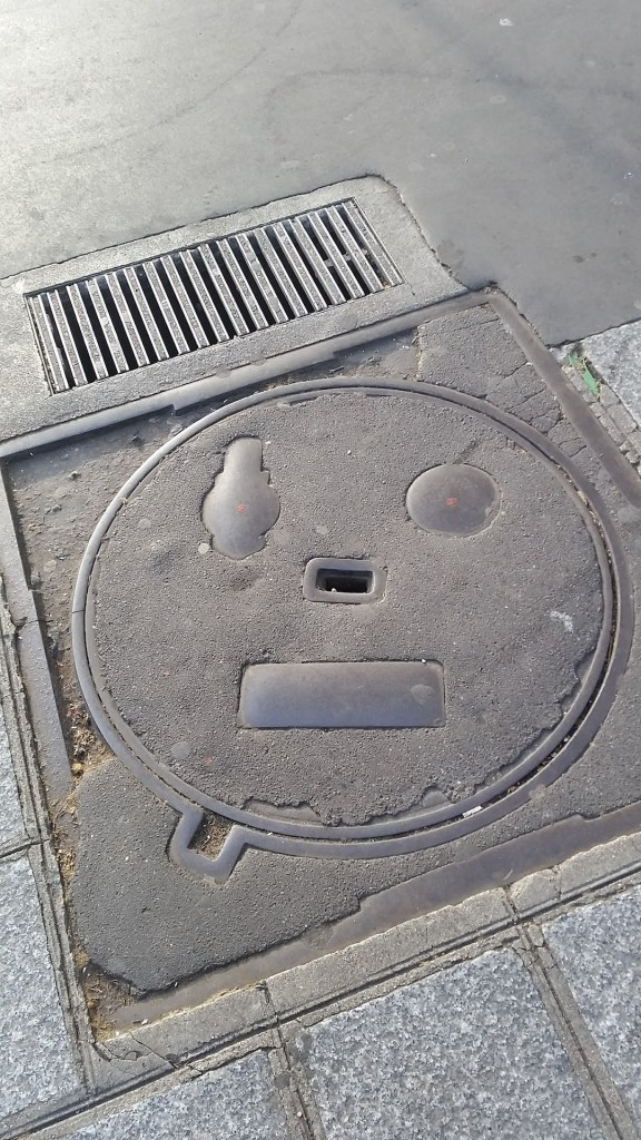 a manhole cover that looks like a surprised face