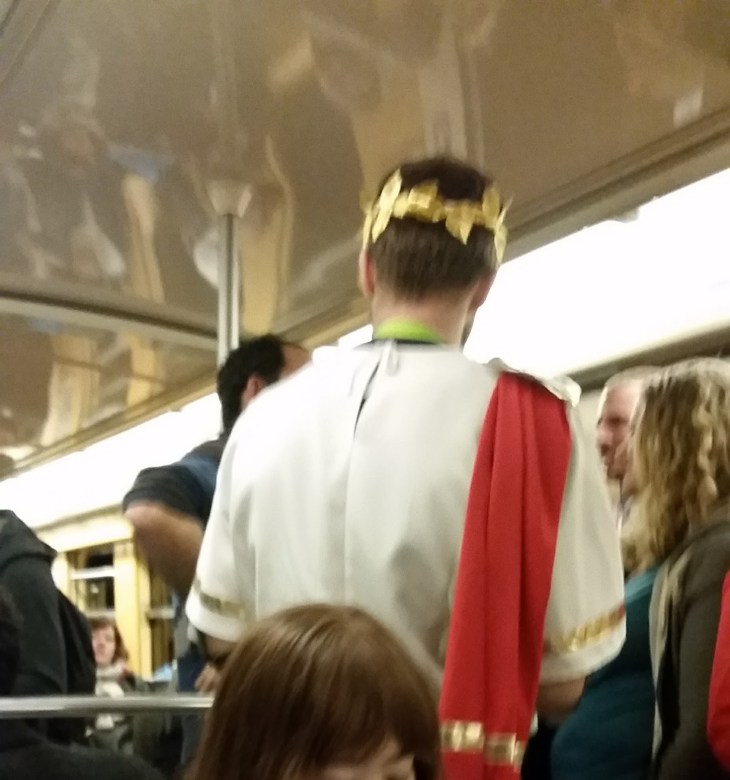 A blurry picture of a man wearing a golden crown of laurel and a white toga like Cesar in the Asterix books