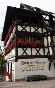 """White half timbered house with flower boxes on the windows and a stone horse trough in front of it. """"Maison des tanneurs"""" is written on it."""