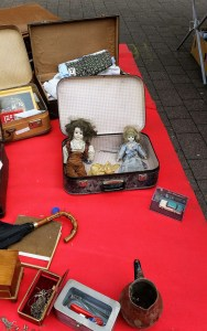 A very old small suitcase, opened. Inside are two dolls with tousled hair.
