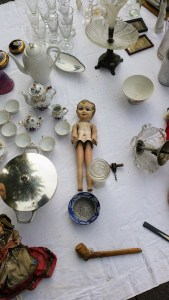 A naked old doll surrounded by old crockery