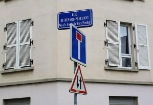 "a street sign ""rue du renard-prechant / Wo d'r Fuchs de Ente predigt"""