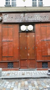 The windows and doors of a bar called ferailleurs are completely closed with rusty metal shutters